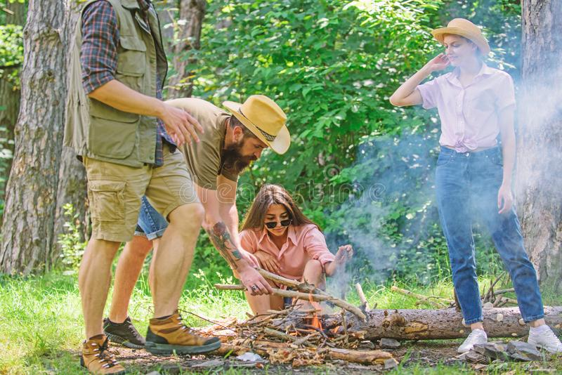 Friends working as team to keep bonfire. Company youth camping forest prepare bonfire for picnic. Add some wood to fire. Company friends or family making royalty free stock image