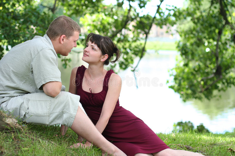 Friendship. Happy young couple relaxing near the river royalty free stock photography