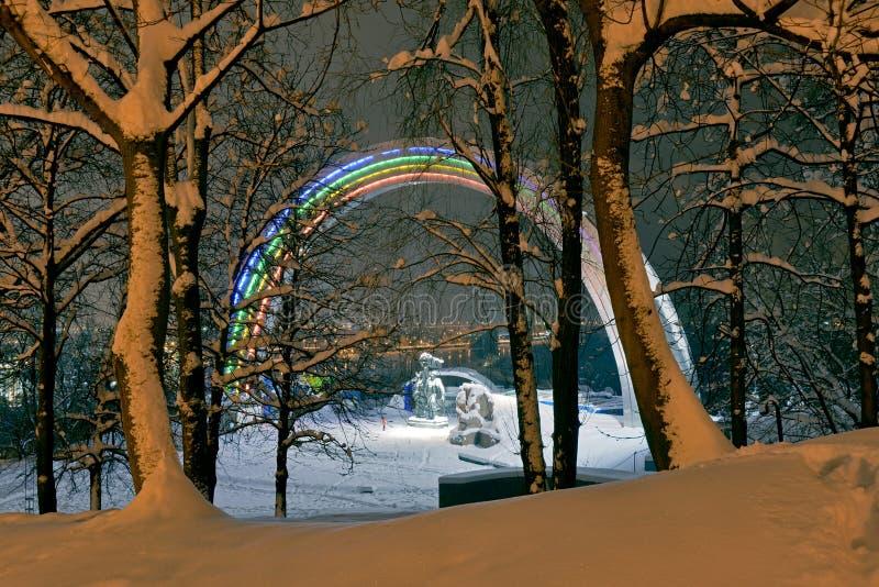 Friendship Arch in Kiev. Winter season in Kiev. Illuminated Friendship Arch and Dnepr river through snowy trees stock photo