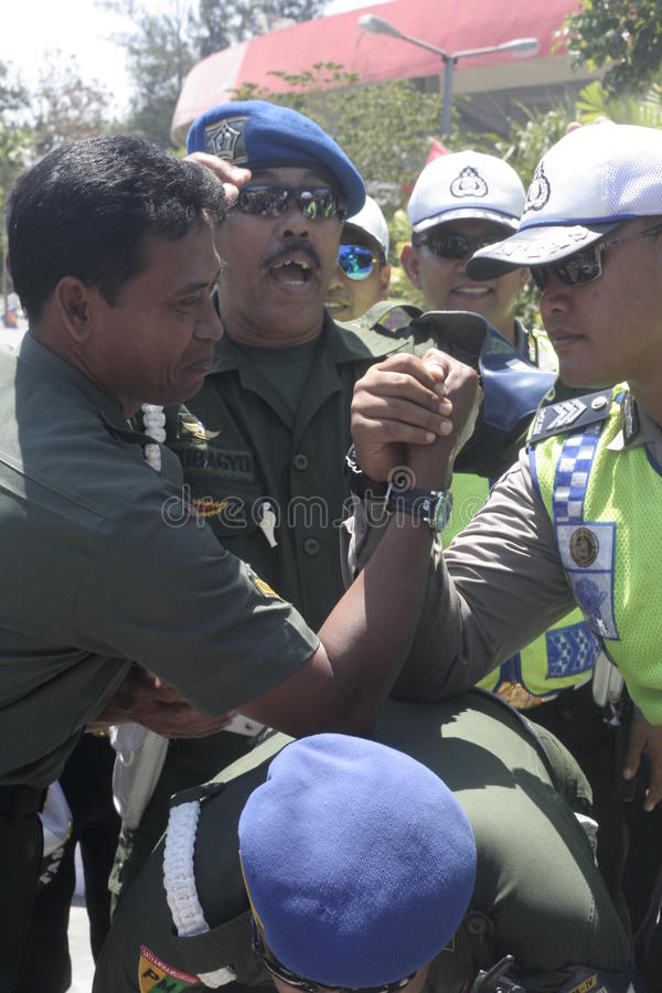 Friendship with arm wrestle between the police and the army in the stadium held their solo Central Java. Symbol of friendship with massaging heads between the royalty free stock images