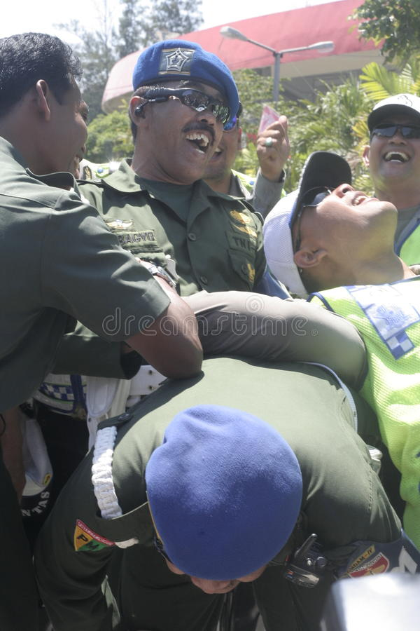 Friendship with arm wrestle between the police and the army in the stadium held their solo Central Java. Symbol of friendship with massaging heads between the royalty free stock photos