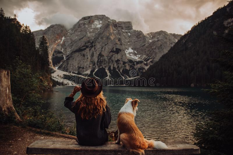 Friendship between child and dog sitting near the lake Lago di Braies stock image