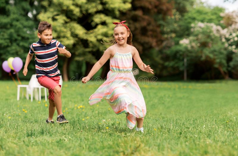 Happy kids playing tag game at birthday party. Friendship, childhood, leisure and people concept - happy kids or friends playing tag game at birthday party in royalty free stock photo