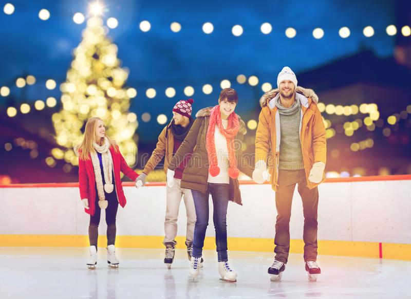 Happy friends on christmas skating rink. Friendship, christmas and leisure concept - happy friends holding hands on skating rink over outdoor holiday lights stock photo
