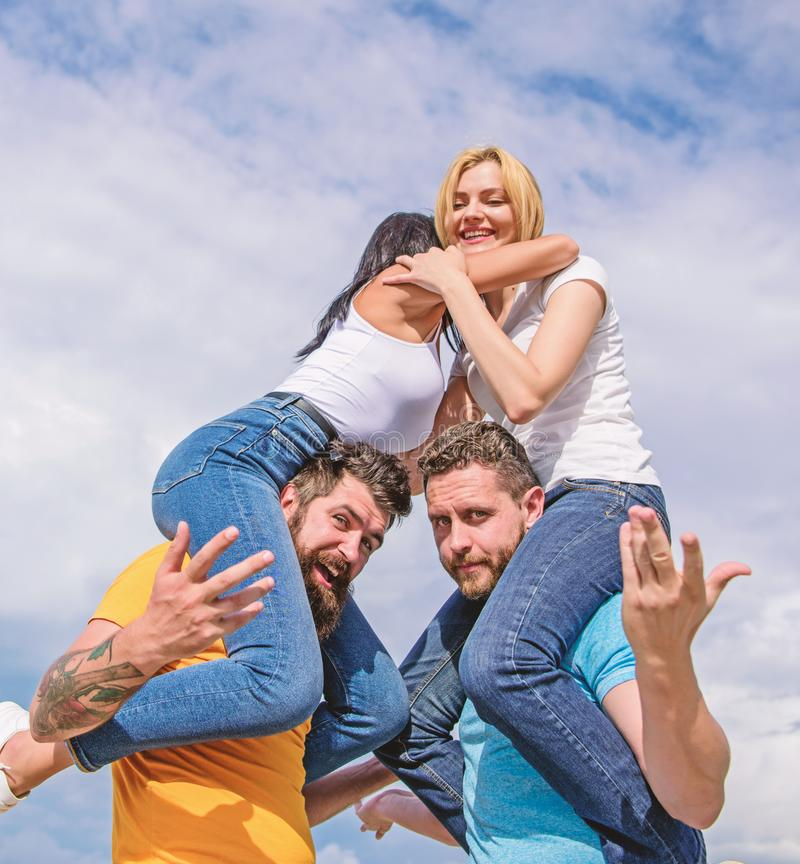 Friendship of families. Twice fun on double date. Couples in love having fun. Men carry girlfriends on shoulders. Summer. Vacation and fun. Couples on double stock image