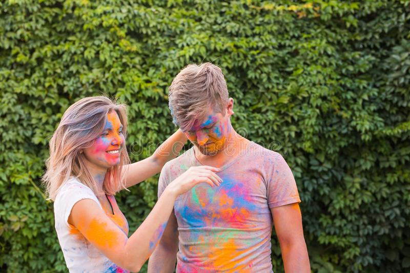 Friendship, festival of holi - young woman play with dirty t-shirt of young man at the festival of holi royalty free stock images