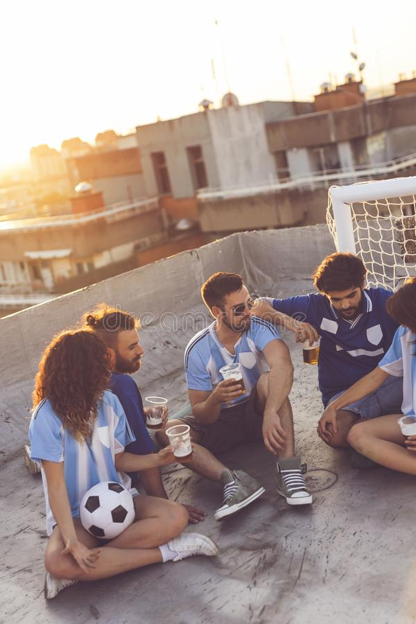 Friendship and football. Group of young people sitting on a building rooftop, wearing jerseys, taking a break from a football match, enjoying sunset over the stock images