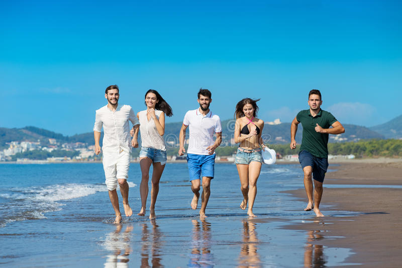 Friendship Freedom Beach Summer Holiday Concept - young people running royalty free stock image
