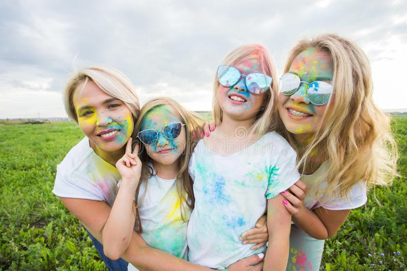 Friendship, holidays, color concept - Portrait of beautiful and happy friends covered in paint over nature background royalty free stock image