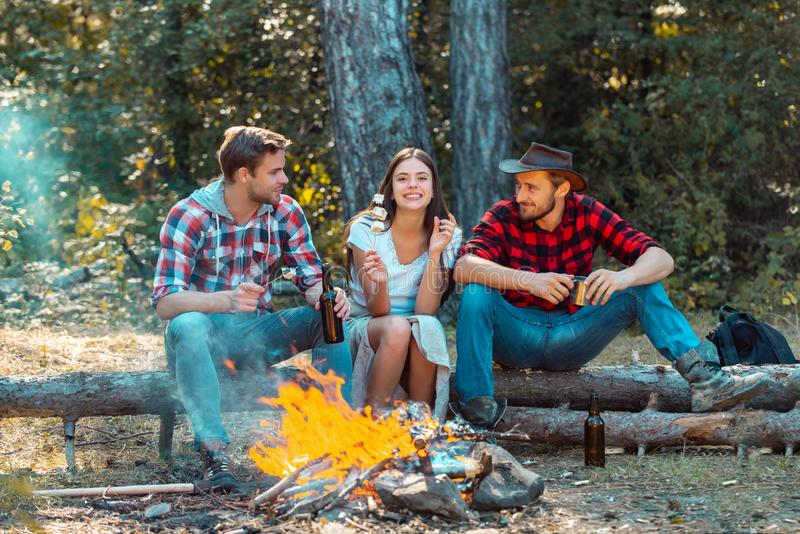 Friendship and leisure concept. Friends hikers watching fire together on camp. Weekend. Good day for spring picnic in royalty free stock photos