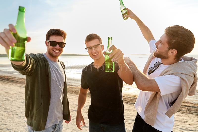 Young men toasting non alcoholic beer on beach stock photo