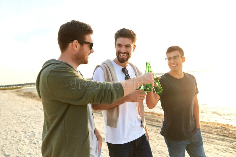 Young men toasting non alcoholic beer on beach royalty free stock image