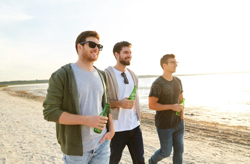 Young men with non alcoholic beer walking on beach stock photos