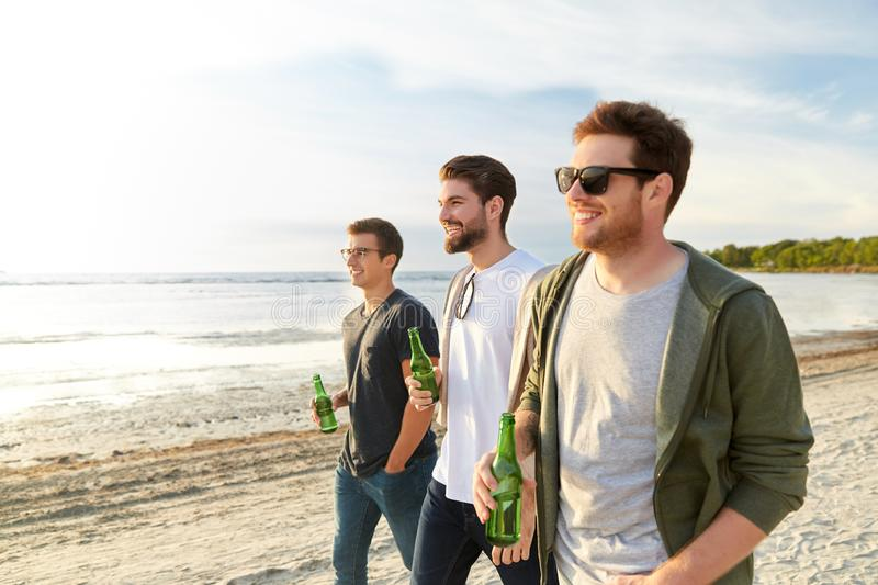 Young men with non alcoholic beer walking on beach royalty free stock images