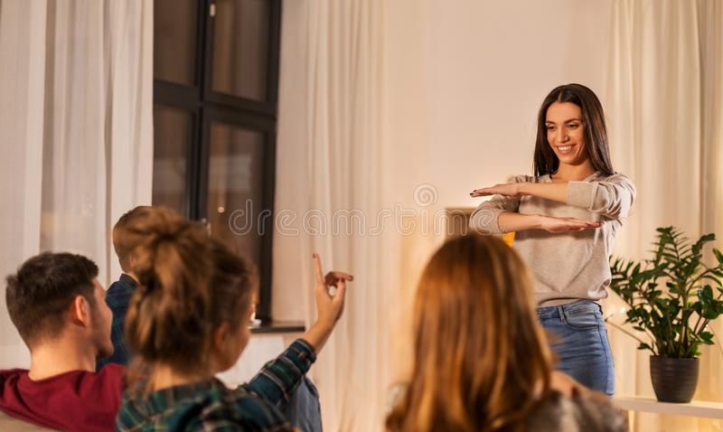 Happy friends playing charades at home in evening stock images