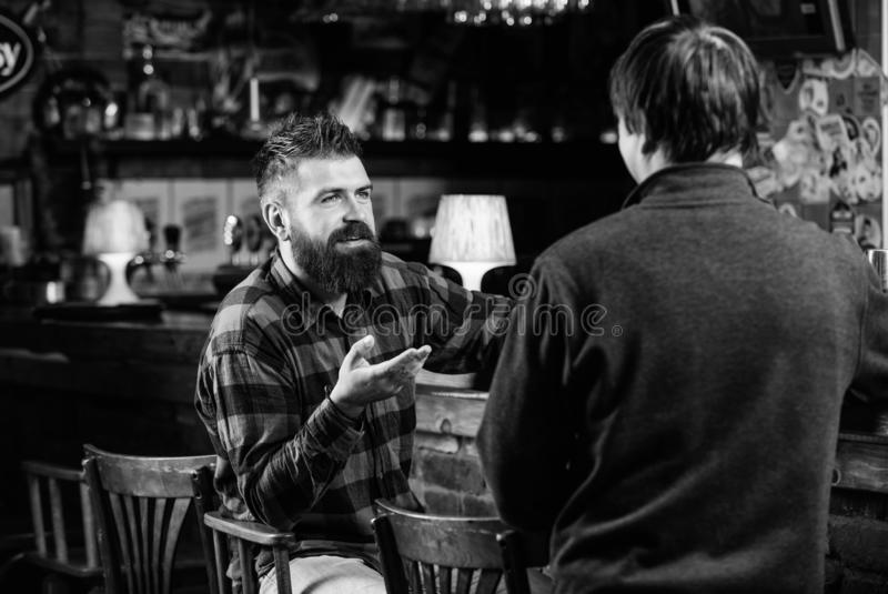 Friendship and leisure. Friday relaxation in bar. Friends relaxing in bar or pub. Interesting conversation. Hipster. Brutal bearded men spend leisure with royalty free stock photo