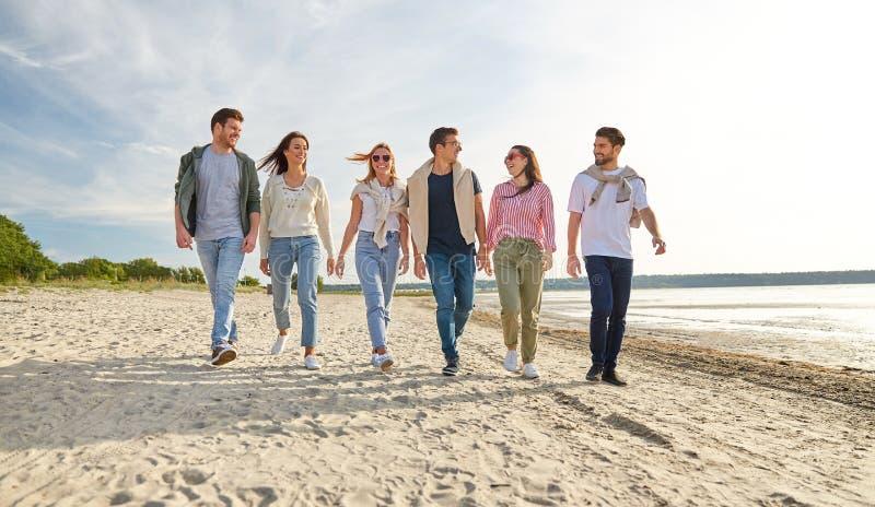 Happy friends walking along summer beach stock photos