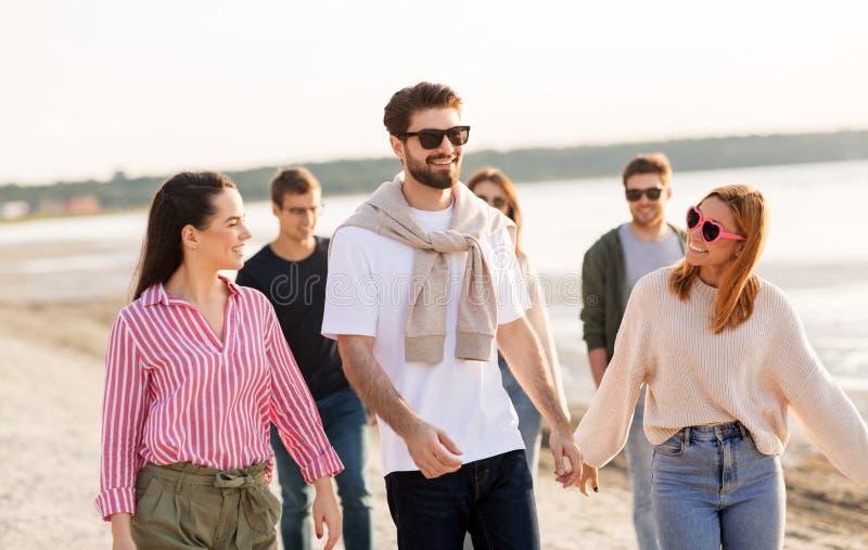 Happy friends walking along summer beach royalty free stock image
