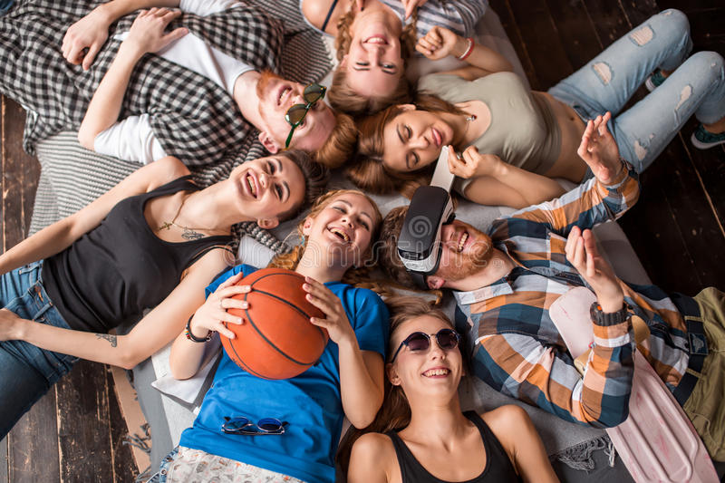 Friendship, leisure, summer and people concept - group of smiling friends lying on floor in circle indoors stock images