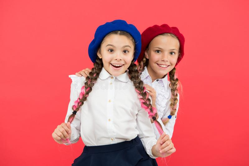Friendship means support. Girls best friends on red background. Cute playful sisters schoolgirls having fun. Kids long royalty free stock image