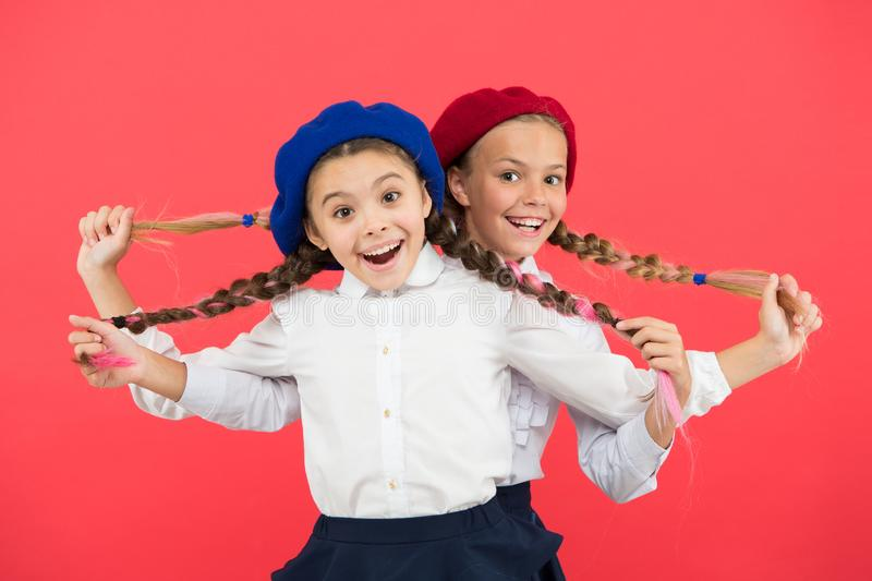 Friendship means support. Kids long braids hairstyle classmates friends. Girls best friends on red background. True royalty free stock images