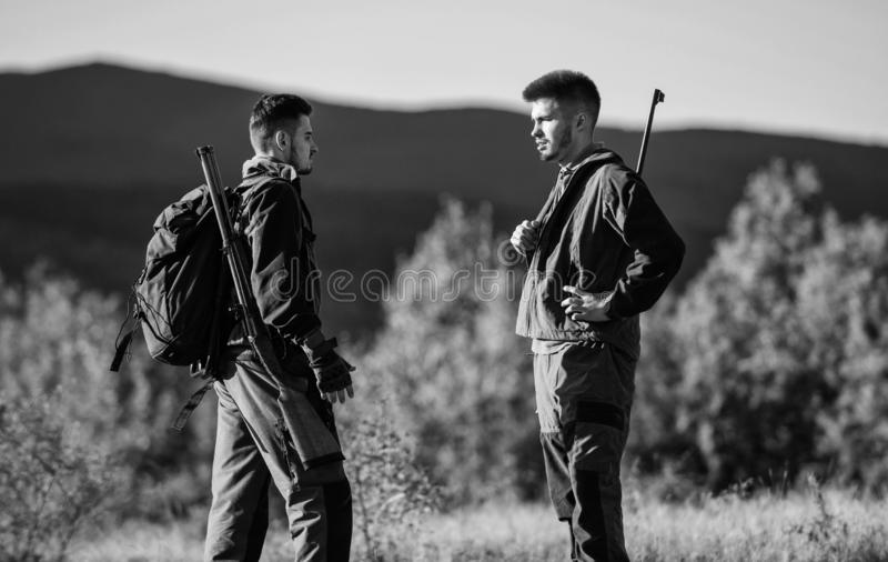 Friendship of men hunters. Military uniform. Army forces. Camouflage. Hunting skills and weapon equipment. How turn. Hunting into hobby. Man hunters with rifle royalty free stock photography
