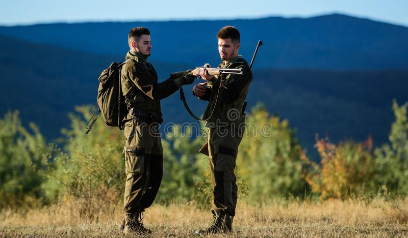 Friendship of men hunters. Military uniform fashion. Army forces. Camouflage. Hunting skills and weapon equipment. How royalty free stock image