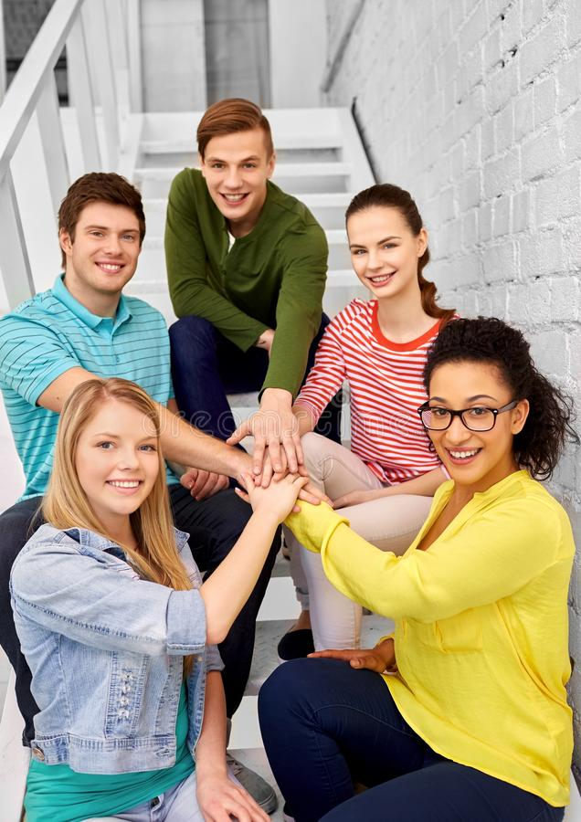 Teenage friends or students stacking hands stock photo