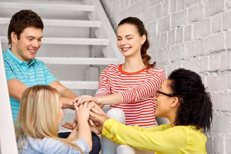 Teenage friends or students stacking hands stock photos