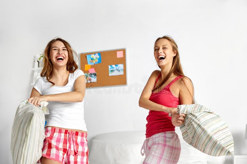 Happy teen girl friends fighting pillows at home stock image