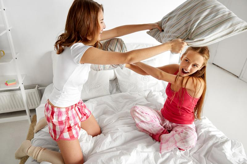 Happy teen girl friends fighting pillows at home royalty free stock photo