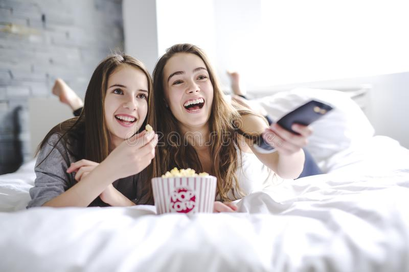 Friendship, people, pajama party, entertainment and junk food concept stock photography