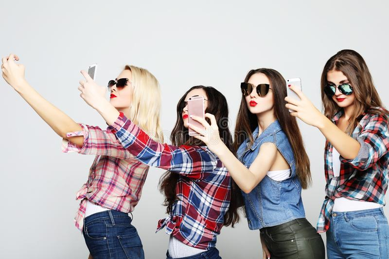 Friendship, people and technology concept - four happy teenage girls with smartphone taking selfie royalty free stock images