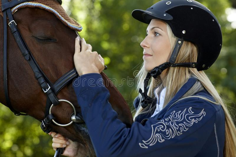 Friendship between rider and horse. Pretty female rider caressing horse forehead with love royalty free stock image