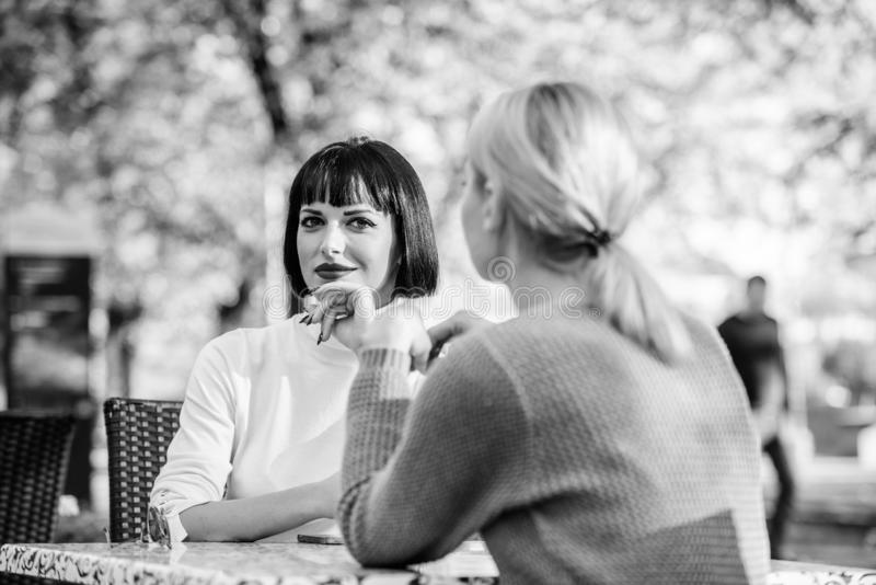 Friendship or rivalry. Girls friends drink coffee talk. Conversation of two women cafe terrace. Friendship friendly royalty free stock photos
