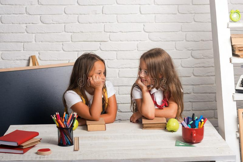 Friendship of small sisters in classroom at knowledge day. Little girls eat apple at lunch break. bored school kids at royalty free stock photography