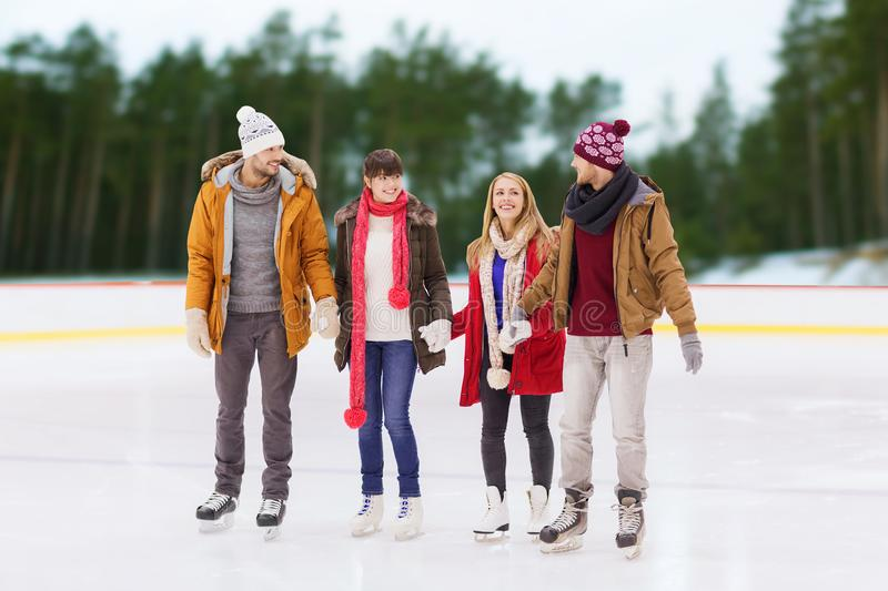 Friends holding hands on outdoor skating rink. Friendship, sport and leisure concept - happy friends holding hands on skating rink over outdoor background royalty free stock photography