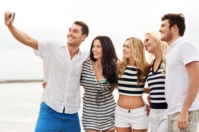Happy friends taking selfie on summer beach stock photos