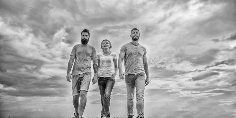 Friendship tested for years. United threesome true friends. Men and woman walks dramatic cloudy sky background. True royalty free stock photo