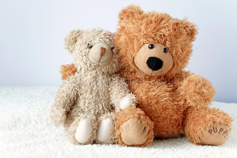 Friendship - two teddy bears holding in one`s arms stock photos