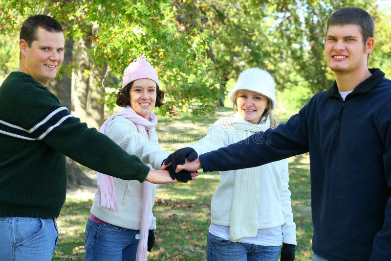 Friendship Unity. Four friends join hand together in park environment. concept for unity and urban lifestyle royalty free stock photo