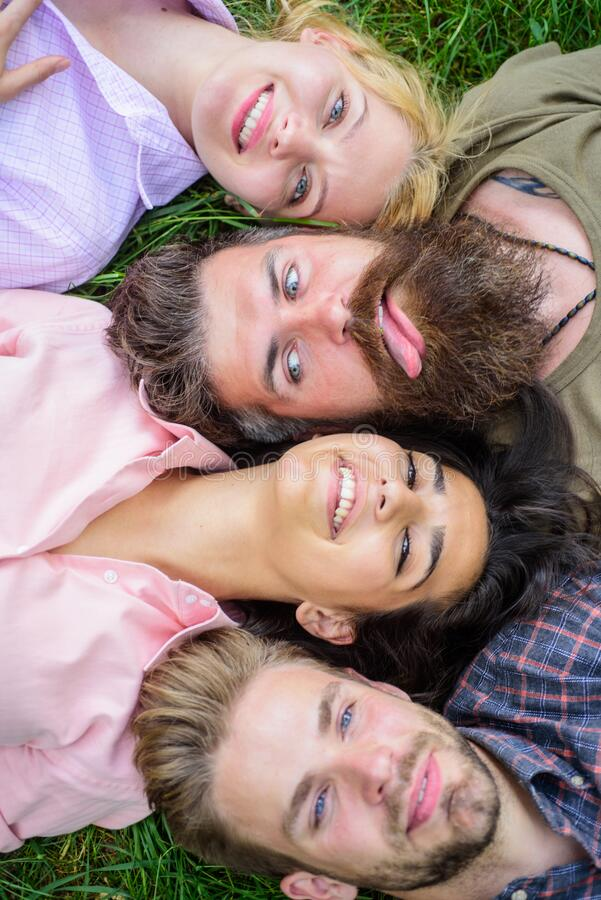 Friendship through whole life. Company friends lay grass top view. Blonde or brutal hipster friends same wave. Youth men. And women head to head. Diversity royalty free stock photography