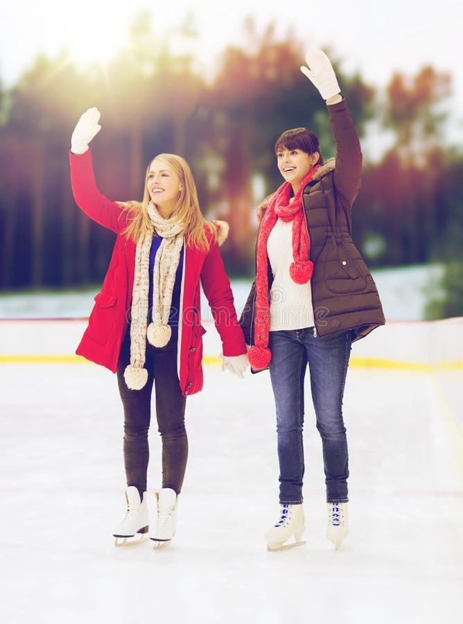 Women or friends waving hands on skating rink. Friendship, winter and leisure concept - two happy women or friends waving hands on skating rink stock photography