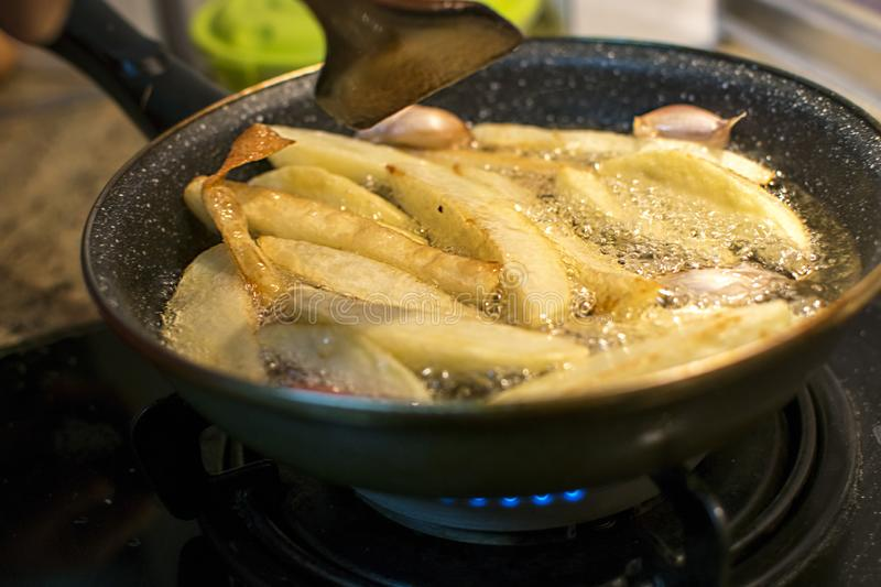 Fries and garlic in process of frying in oil boiling on old cast iron pan stock images
