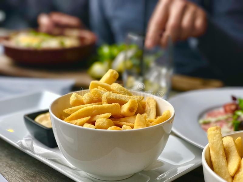 Fries with mayonaise in restaurant. Plate with fries and mayonaise in restaurant stock photography