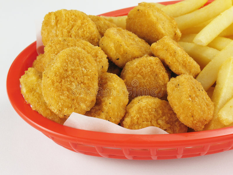 Fries & Nuggets. Basket of chicken nuggets with french fries royalty free stock images