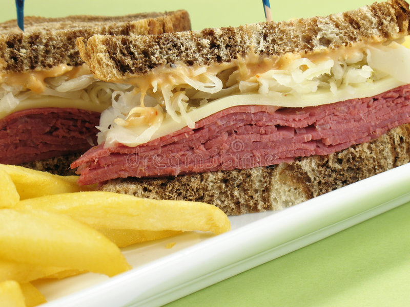 Fries & Reuben. Reuben sandwich with corned beef, melted swiss cheese, sauerkraut, and thousand island dressing on marble rye bread. Served with french fries royalty free stock photos