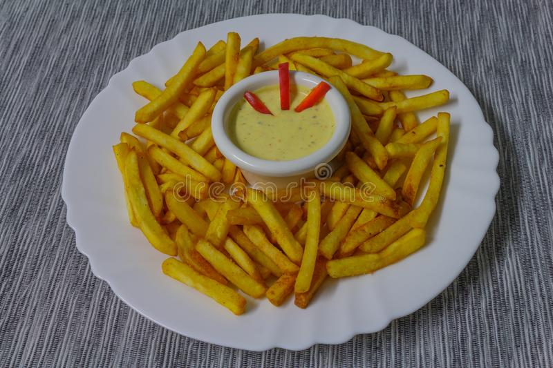 Fries on white plate bowl with dressing royalty free stock photography