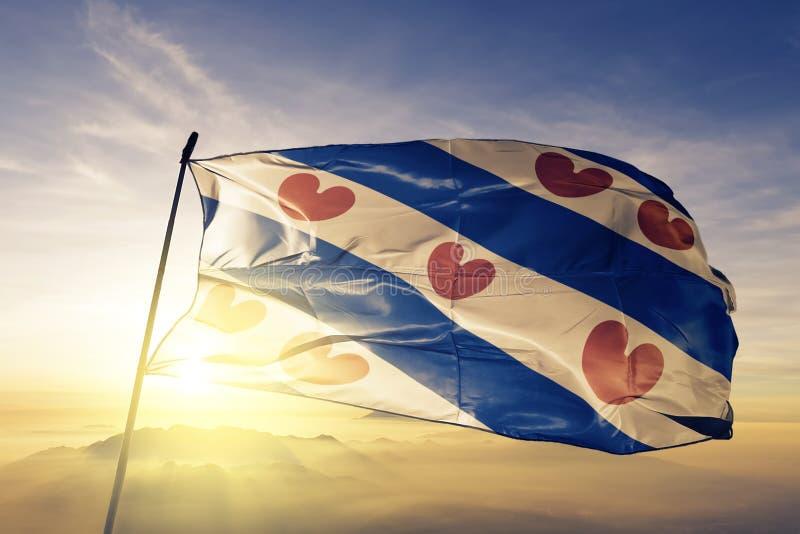 Friesland landskap av tyg för torkduk för Nederländernaflaggatextil som vinkar på den bästa soluppgångmistdimman stock illustrationer