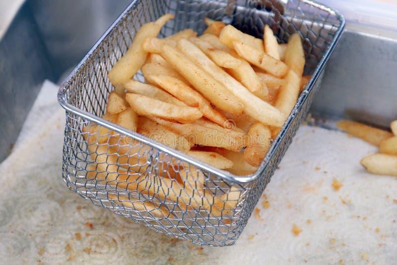 Frieten, de olie van Mandfrieten op de witte, Smakelijke frieten van het papieren zakdoekjeblad in de selectieve nadruk van de me stock fotografie